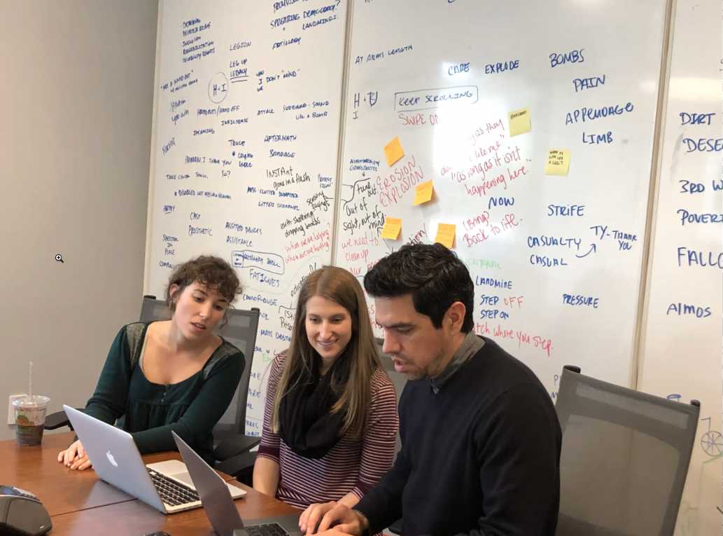 three Mighty Citizen team members working at a desk with a whiteboard in the background that has strategy notes all over it