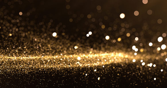 gold glitter in an out of focus on a dark background
